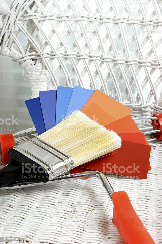 Paint samples and brush in white wicker chair royalty-free stock photo
