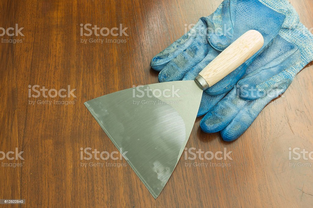 paint scraper with wood handle and working gloves. stock photo