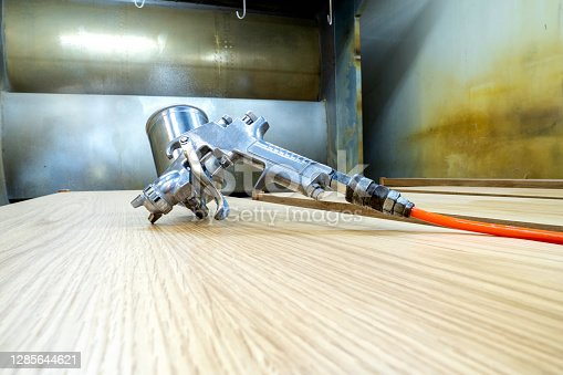 istock Paint spray gun, an industrial type, is placed on the table top, in the spray chamber. 1285644621