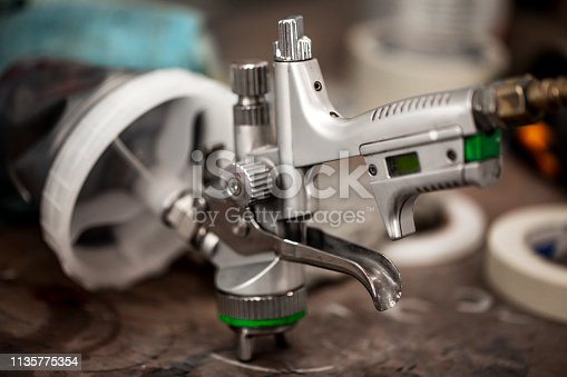 A close-up of a paint spray gun laid on it's front part on the table in a workshop.