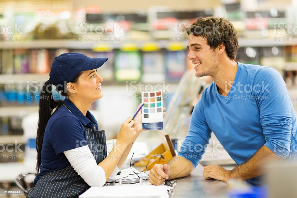 paint store assistant helping customer choose paint color stock photo