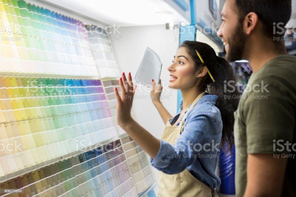 Paint store employee assists male customer stock photo