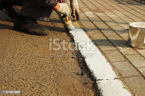 paint the kerbs with white paint. urban service. profession, close-up