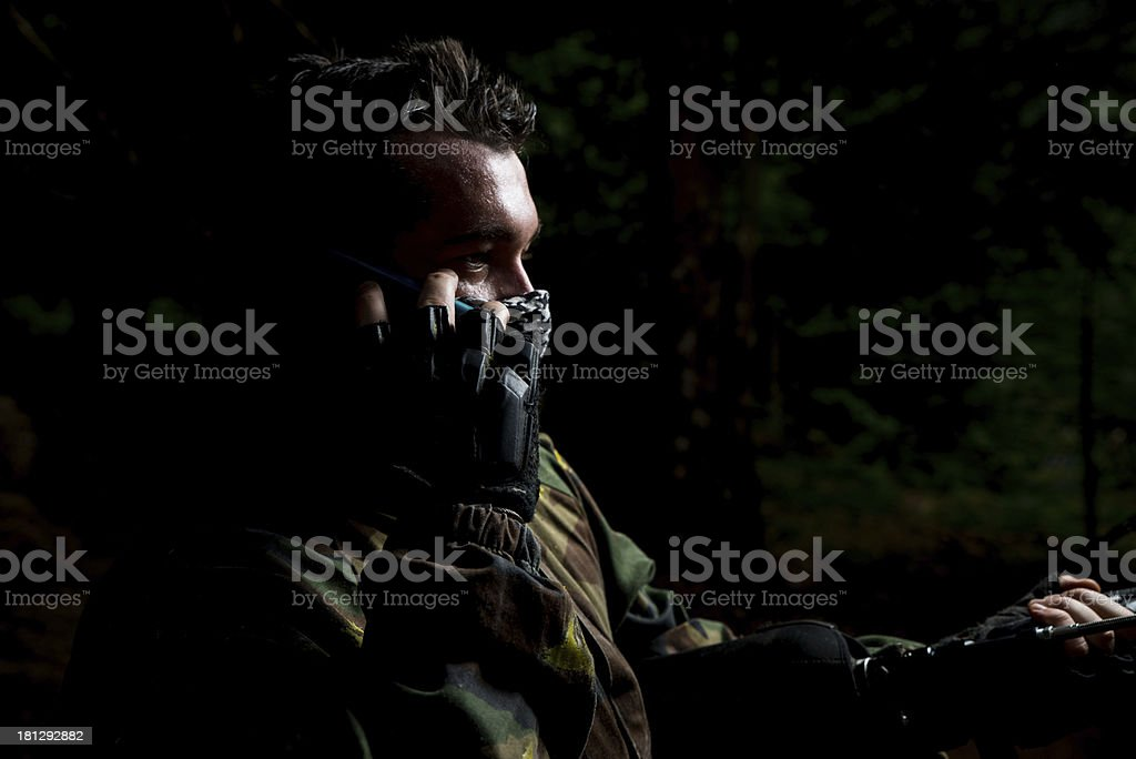 Paintball player calling someone at the phone stock photo