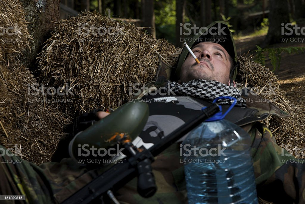 Paintball player resting and smoking a cigar stock photo