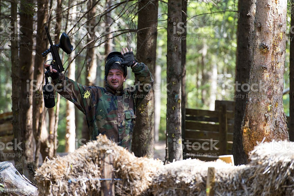 Paintball player resting from playing around stock photo
