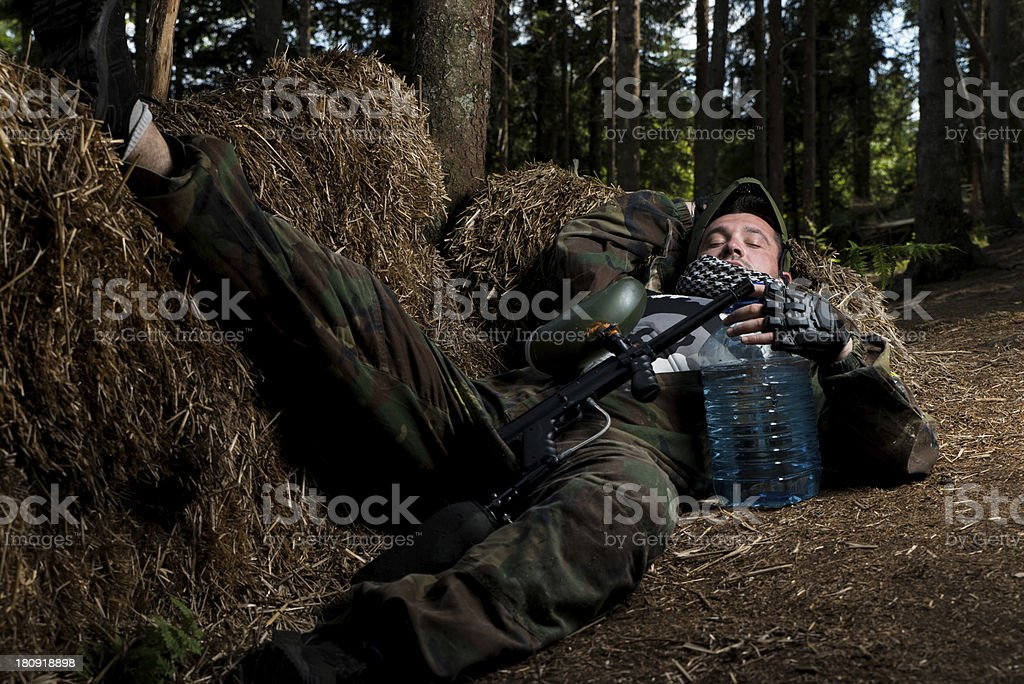 Paintball player resting on the ground stock photo