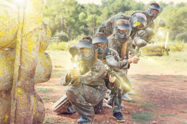 Equipe de paintball correndo com armas marcador - foto de acervo
