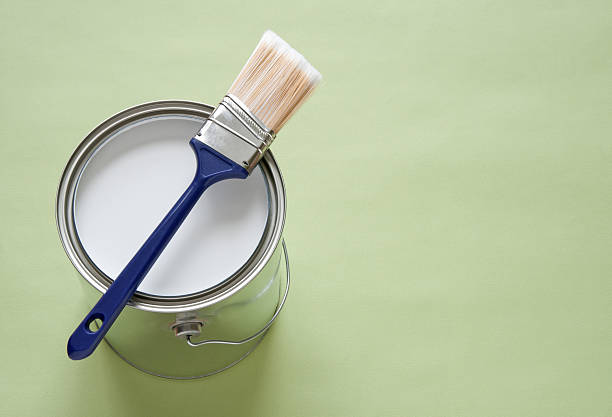 Paintbrush and a can of white paint on green background stock photo