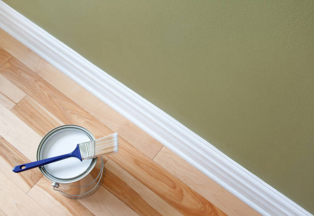 Paintbrush and a can of white paint on wooden floor stock photo