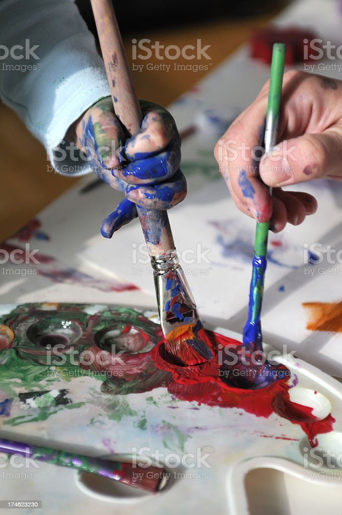 Paintbrush and dirty hands royalty-free stock photo