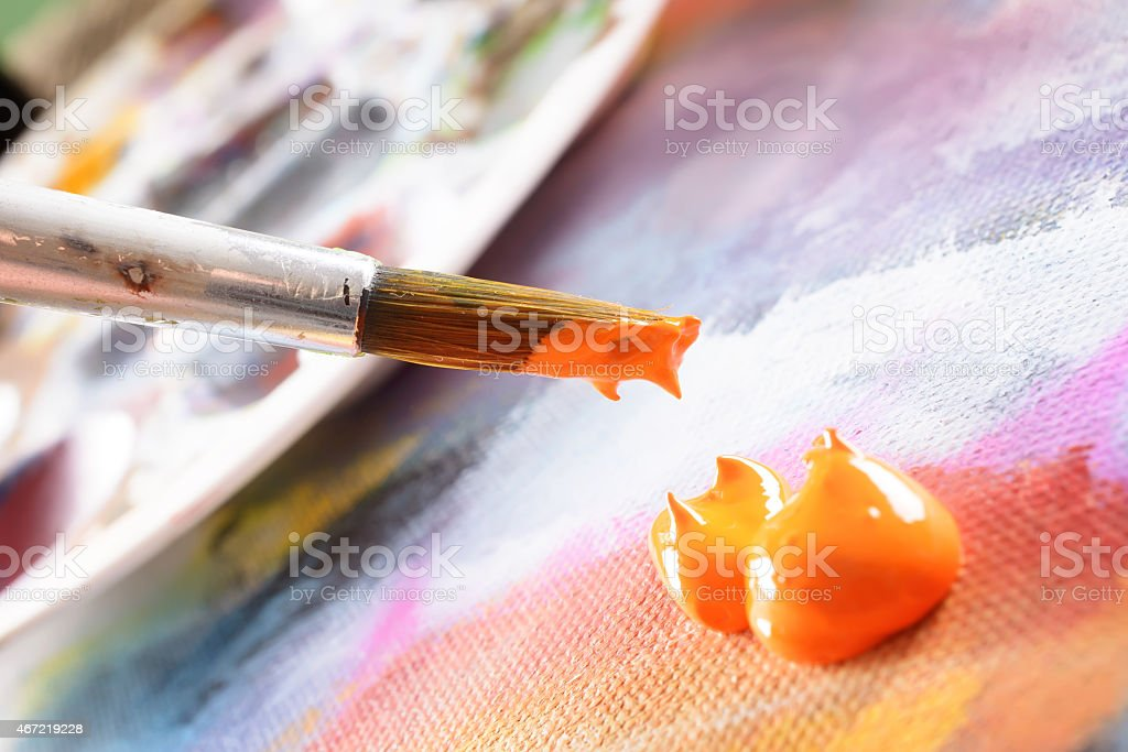 Paintbrush being dipped into orange paint stock photo