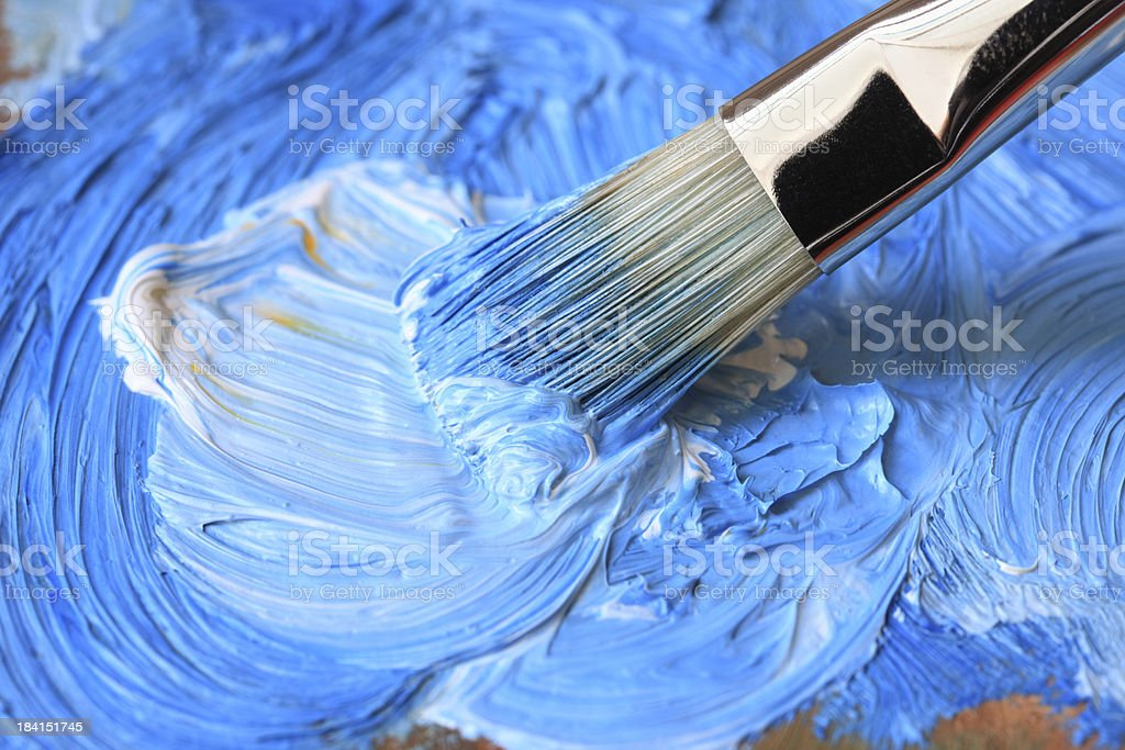 Paintbrush with blue oil paint on a classical palette stock photo