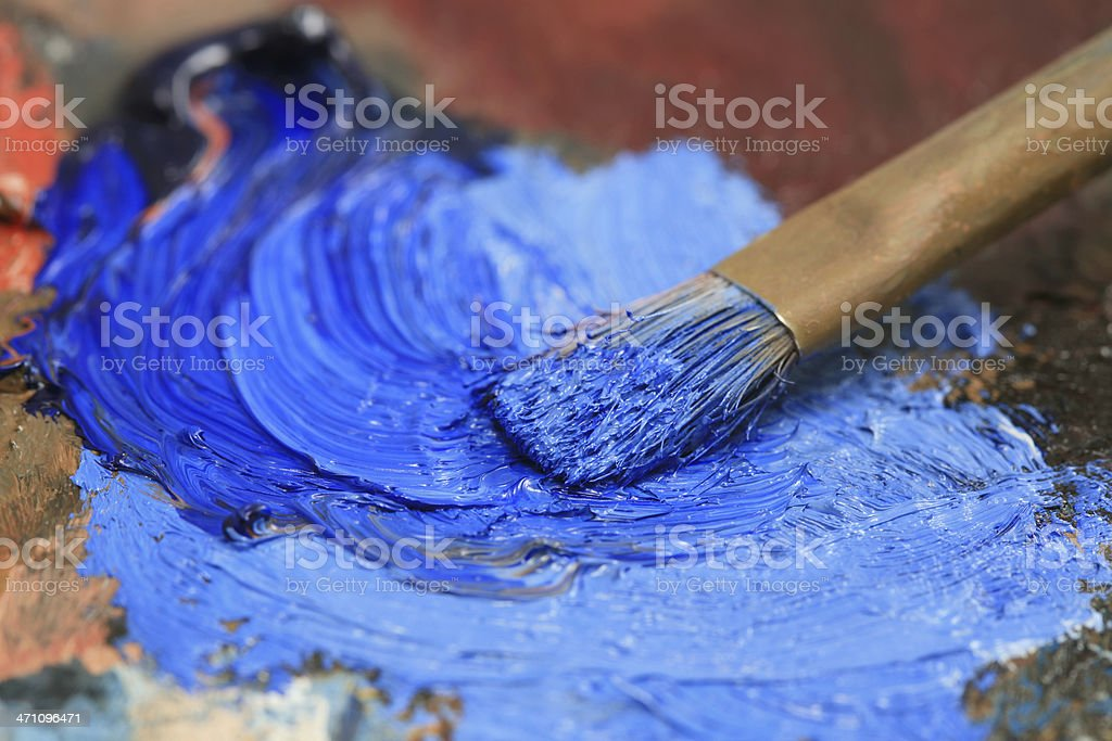 Paintbrush with blue oil paint on a classical palette royalty-free stock photo