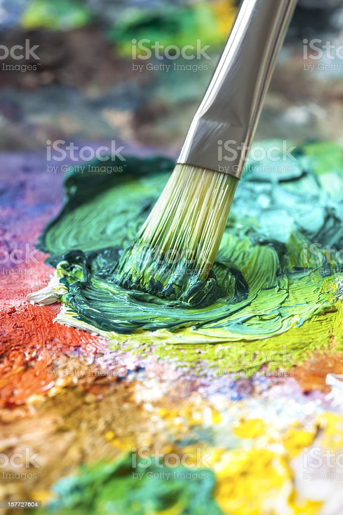 Paintbrush with green oil paint on a classical palette stock photo