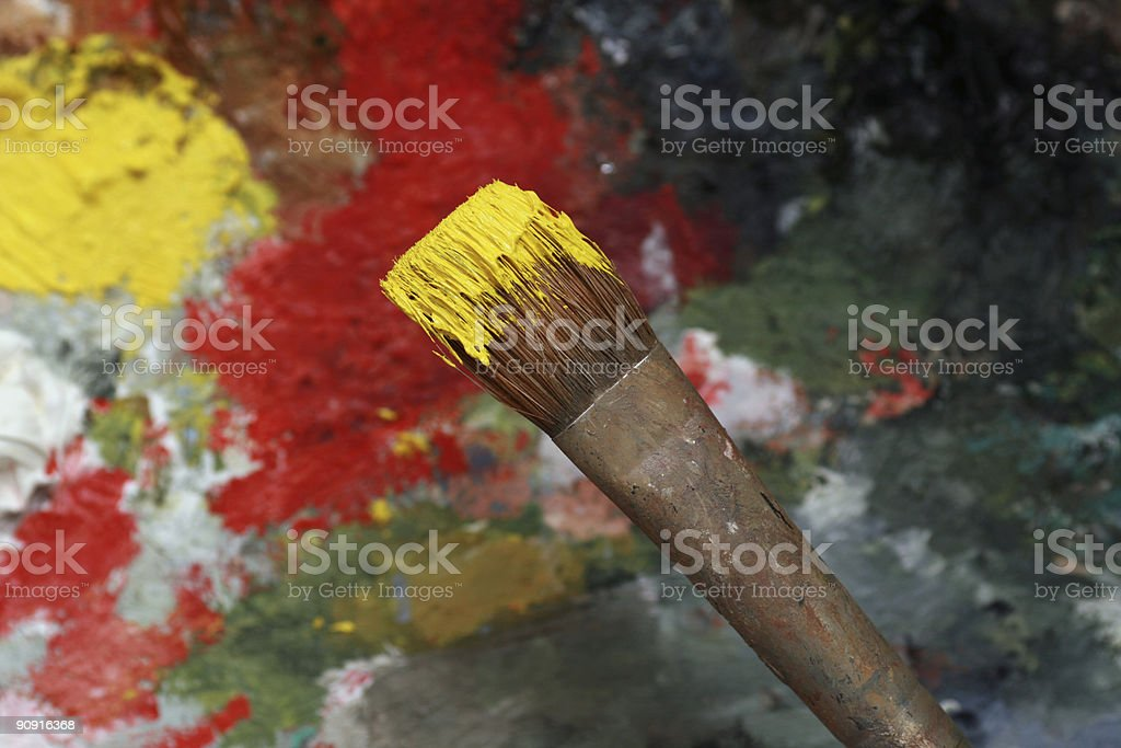 Paintbrush with yellow oil paints and a palette royalty-free stock photo