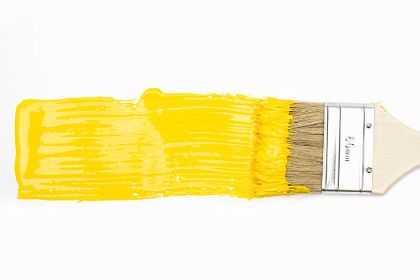 paintbrush with yellow paint - stroking stock pictures, royalty-free photos & images