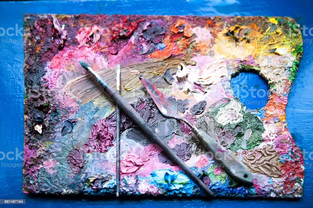 Paintbrushes and palette-knife on the palette stock photo