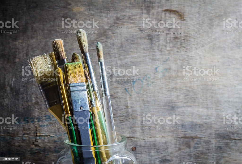 Paintbrushes in a glass jar stock photo