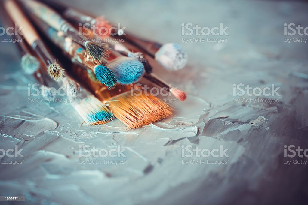 Paintbrushes on artist canvas covered  with oil paints stock photo