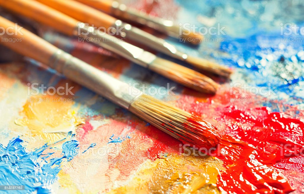 Paintbrushes with red oil paint on a classical palette stock photo