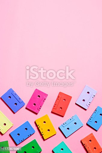 Red, green, blue, yellow retro audio cassettes flat lay background
