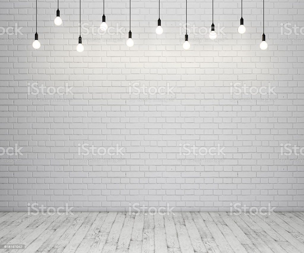 Painted brick wall and wooden floor with glowing light bulbs stock photo