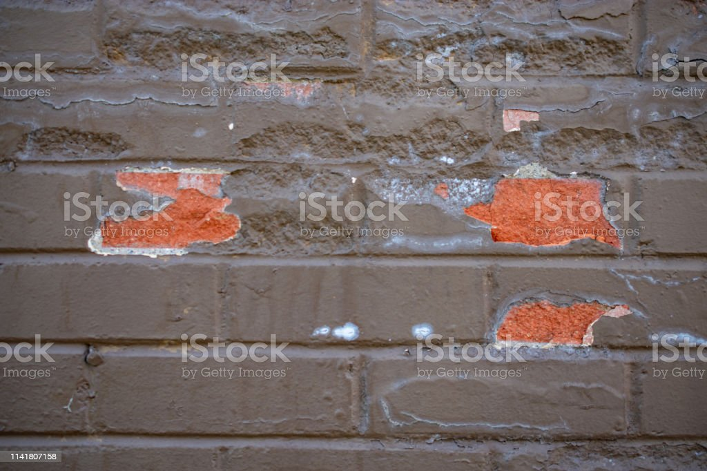 painted brick with paint chipped off stock photo