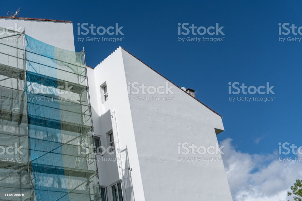 Painted facade of a building with metallic scaffolding wall and blue...