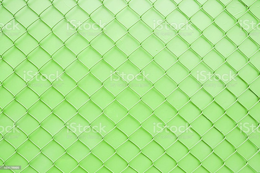 Painted Chain Link Fence Texture Pattern Against Bright Green Wall royalty-free stock photo