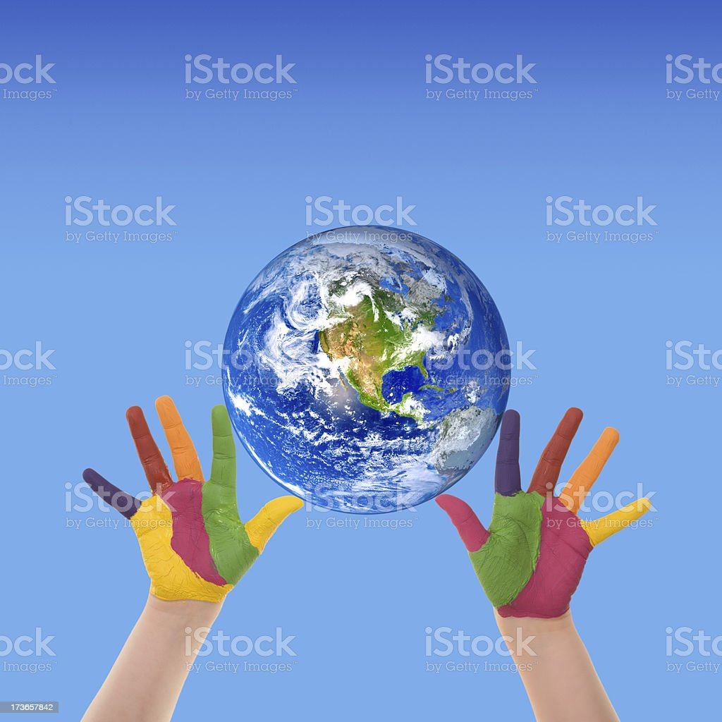 Painted child hands holding planet Earth against blue background royalty-free stock photo