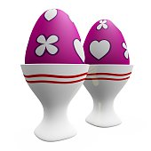 Two egg cups, decorated with pink and blue stripes with white spots and holding brown eggs on white table with light blue background.  Copy space above.