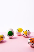 Colorful painted easter eggs on pink and white background