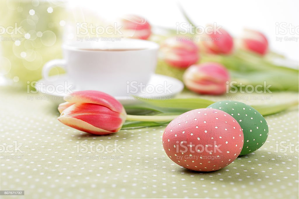 Painted eggs and tulips around a tea cup stock photo