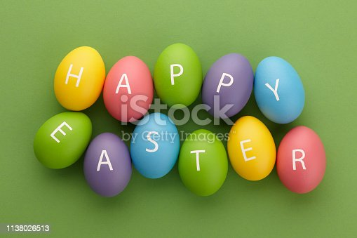 Colorful painted eggs with letters arranged in Happy Easter greeting on green background. Holiday concept.