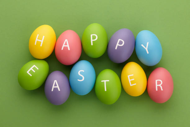 Painted eggs arranged in Happy Easter greeting Colorful painted eggs with letters arranged in Happy Easter greeting on green background. Holiday concept. easter stock pictures, royalty-free photos & images