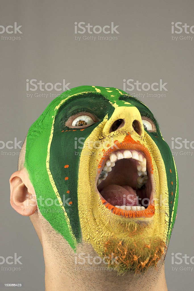 Painted face of young man expresing fear. Tribal war mask. Dominating...