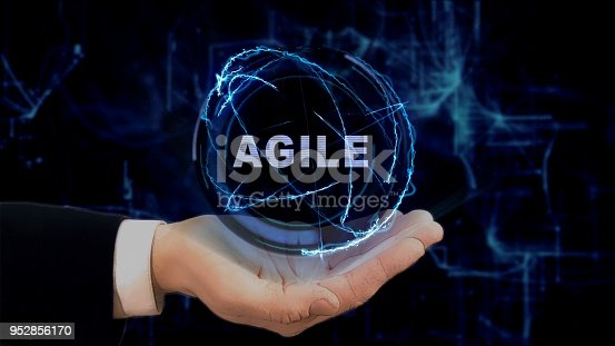 istock Painted hand shows concept hologram Agile on his hand 952856170