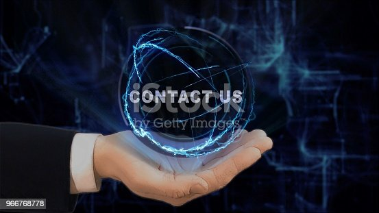 Painted hand shows concept hologram contact us on his hand. Drawn man in business suit with future technology screen and modern cosmic background