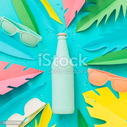 istock Painted in blue beer or cocktail bottle lies among sunglasses and palm tropical leaves 1022075462