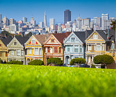 Classic postcard view of famous Painted Ladies, a row of colorful Victorian houses located at scenic Alamo Square, with the skyline of San Francisco in the background on a beautiful sunny day with blue sky in summer