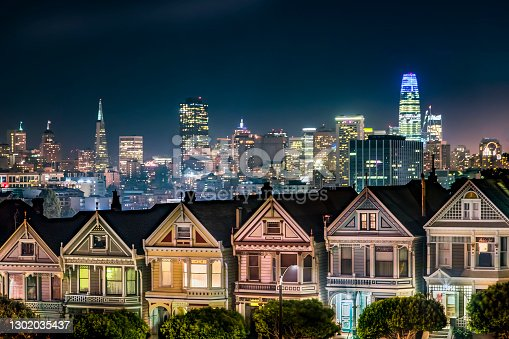 Backed by the night skyline of the city of San Francisco, California, the Victorian era houses near Alamo Square Park, are painted in colors to accentuate their architectural details.
