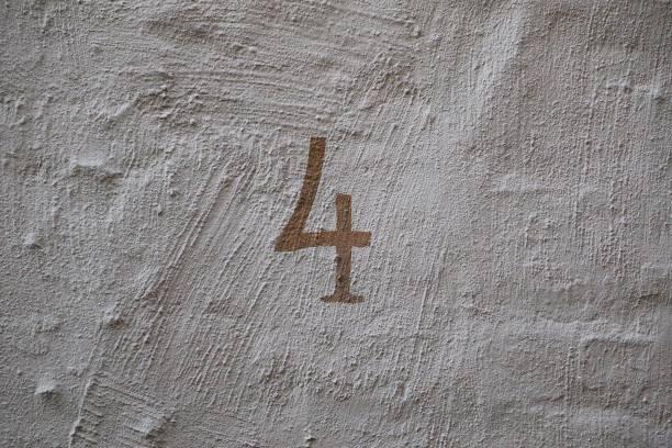 bemalte Nummer vier an einer weißen Hauswand – Foto