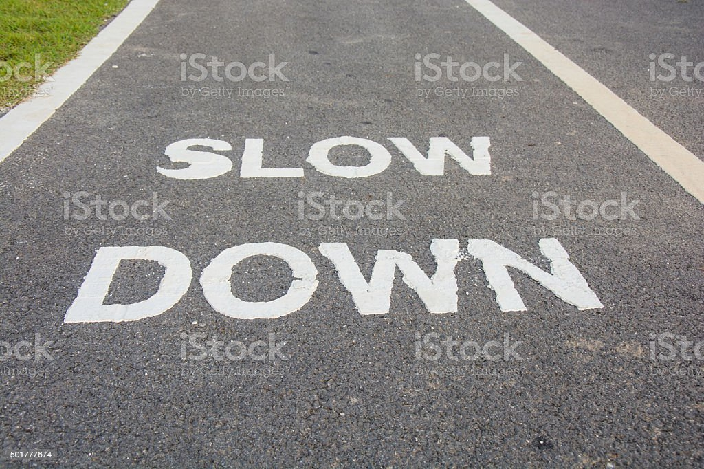 SLOW DOWN painted on the bike lane stock photo