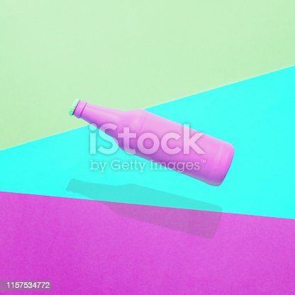 istock Painted purple beer bottle flying above a colored background 1157534772