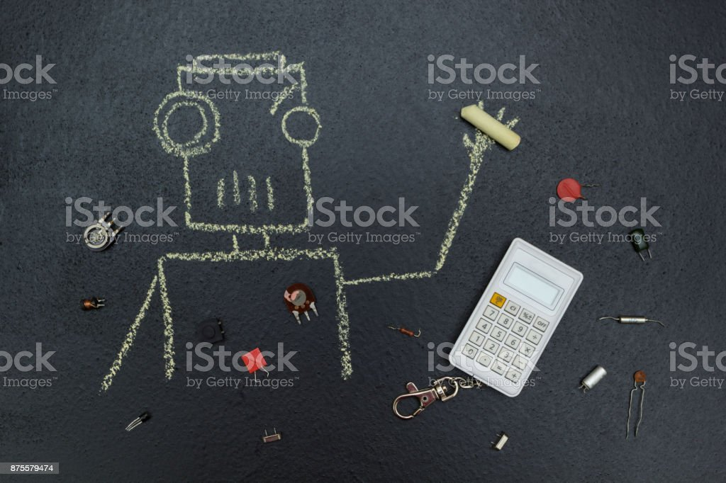 A painted robot with a piece of chalk in hand, a calculator and retro radio parts. stock photo
