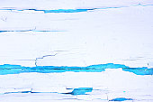 istock Painted rough wooden background, old wall with cracked paint white on blue backdrop. 1022352162