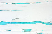 istock Painted rough wooden background, old wall with cracked paint white on turquoise backdrop. 1022917228