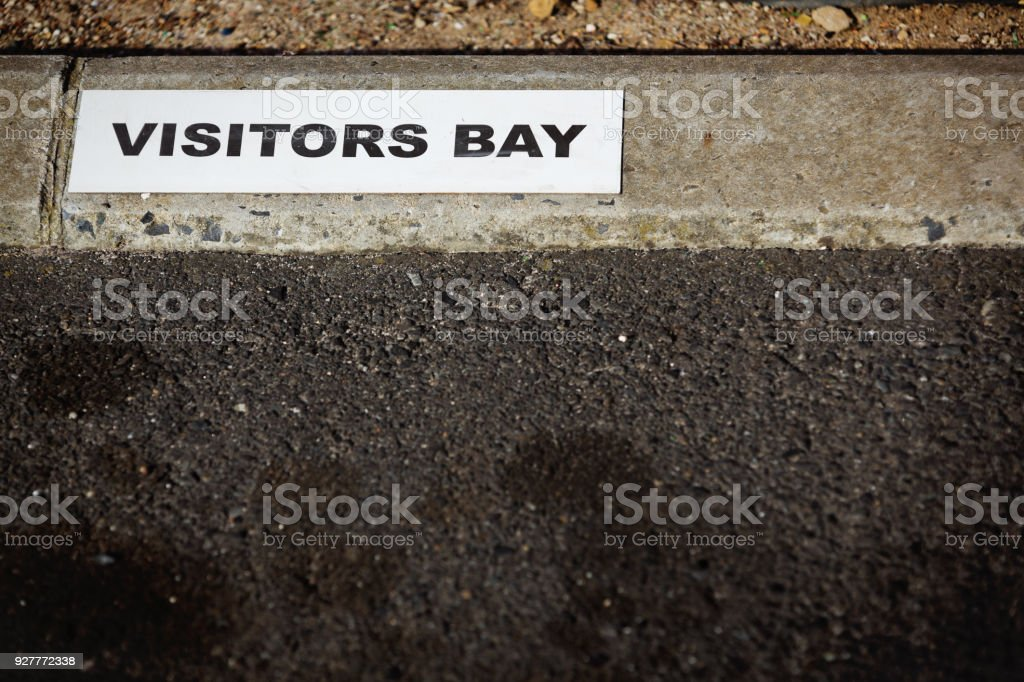 Painted sign on curbstone reads 'Visitors Bay' stock photo