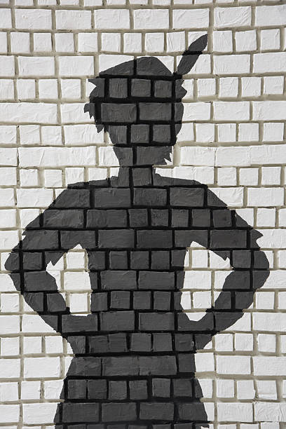 Painted silhouette Peter Pan on wall Painted silhouette Peter Pan on white brick wall peter pan stock pictures, royalty-free photos & images